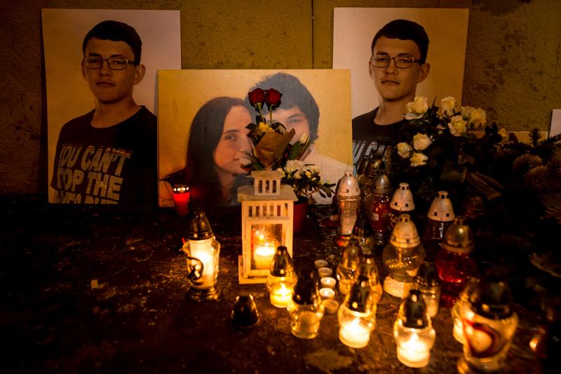 Kerzen und Blumen neben Fotos von Martina Kušnírová und Ján Kuciak