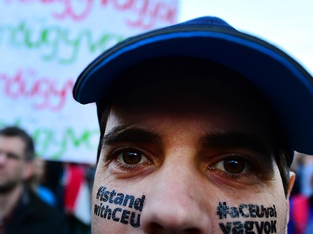 """Ein junger Mann bei einer Demo für die CEU, auf seinem Gesicht steht """"I stand with CEU"""""""