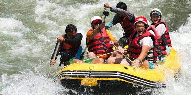 Touristen in einem Raftingboot mit zwei Guides