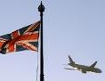Ein Flugzeug fliegt an einer britischen Flagge am Victoria Tower des Palace of Westminster vorbei