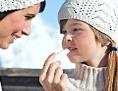 Einem Kind wird Lippenbalsam aufgetragen