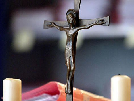 Ein Richtertisch mit zwei Kerzen, einem Kruzifix und Akten