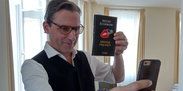 Rocko Schamoni macht ein Selfie von sich mit seinem Buch