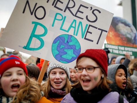 """Für Klimaschutz streikende Jugendliche mit einem Plakat: """"There's no Planet B"""""""