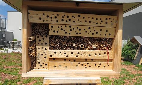 Insektenhotel aus Holzblöcken und Halmen