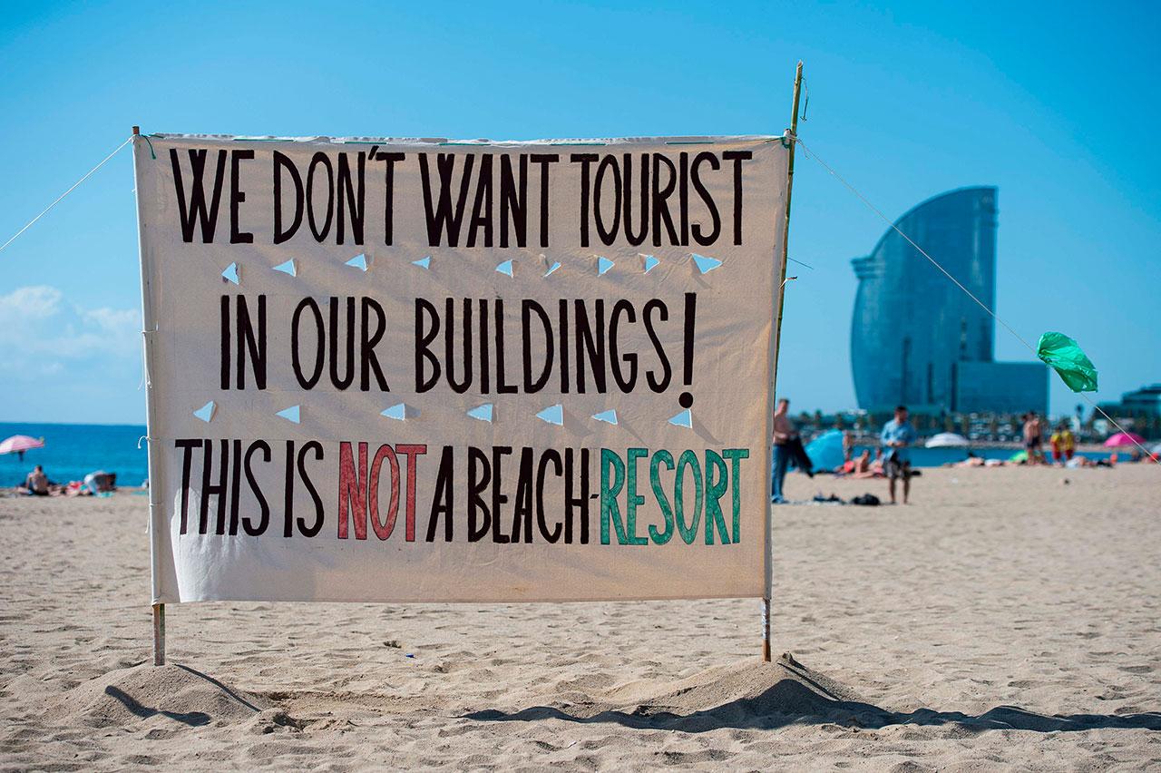 Plakat am Strand, das sich gegenTouristen richtet