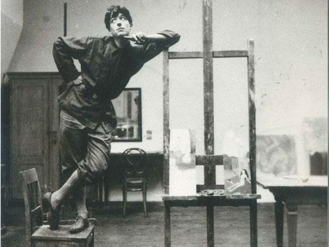 Arik Brauer an der Akademie der Bildenden Künste auf einem Stuhl stehend