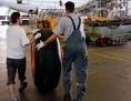 zwei Mechaniker rollen ein Flugzeugrad durch einen Hangar
