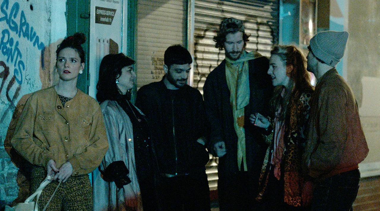 Sechs junge Erwachsene abends beim Ausgehen, sie stehen vor einer Hauswand