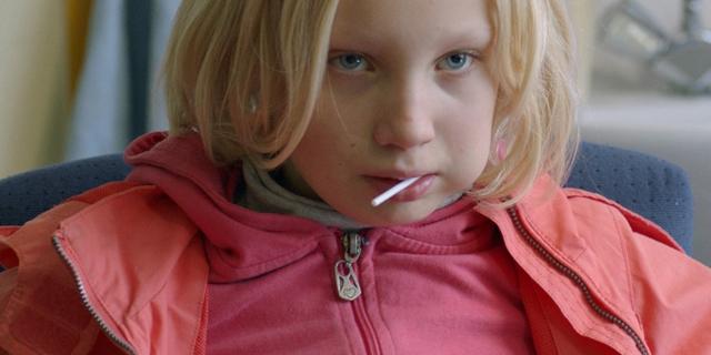 Kind mit Lutscher im Mund