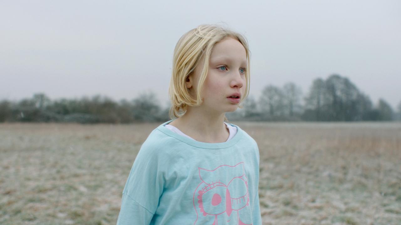 Ein Mädchen steht auf einem Feld