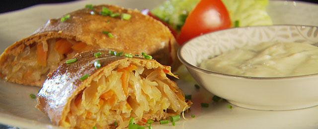 Dinkelkrautstrudel auf Teller mit Käsesauce in Schüssel