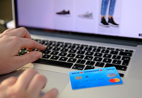 Debitkarte liegt auf Notebook, im Hintergrund eine Shopping-Website