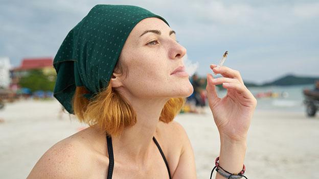 Frau raucht am Strand