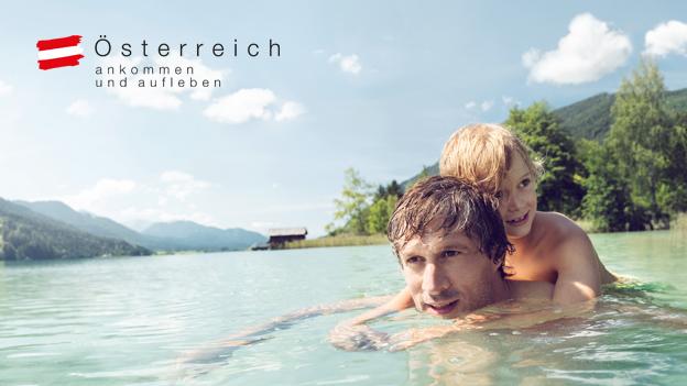 Vater mit Kind schwimmt im Weissensee