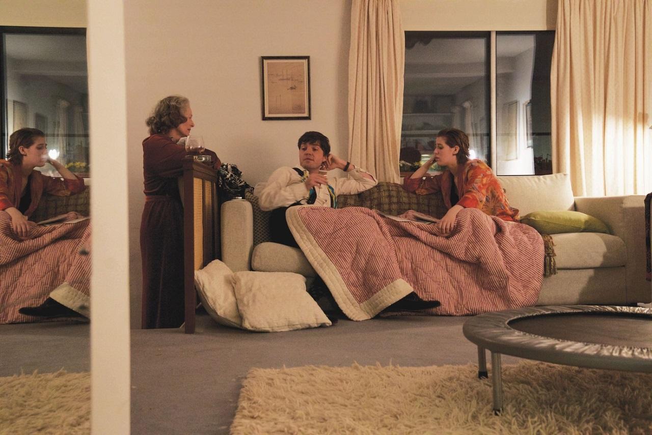 Junge Frau und junger Mann sitzen auf einem Sofa unter einer Decke im Wohnzimmer, die Mutter kniet plaudernd daneben, Im Nebenzimmer ist eine andere junge Frau.