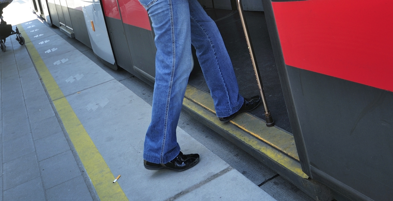 Füße neben Krücke in Straßenbahn-Türe