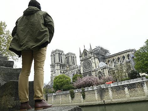 Ein Betrachter vor der Kirche Notre-Dame in Paris nach dem Brand