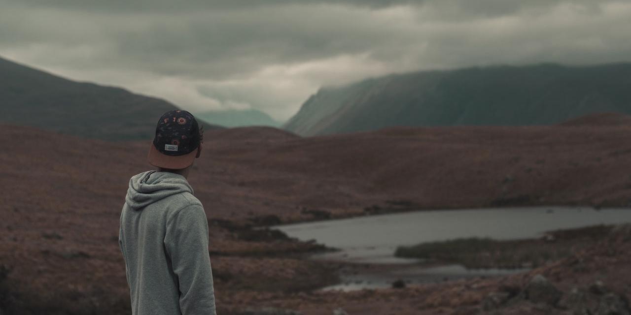 Junger Mann mit Kappe starrt in eine triste Landschaft
