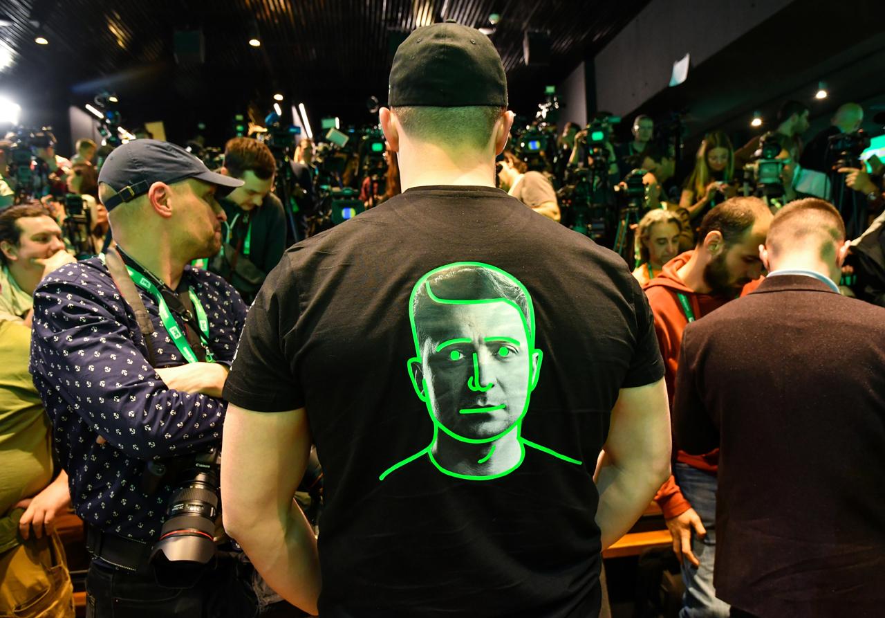 Wahlabend: viele Fotografen. Ein Mann steht mit dem Rücken zu uns, auf seinem T-Shirt ist das Gesicht Selenskis zu sehen.