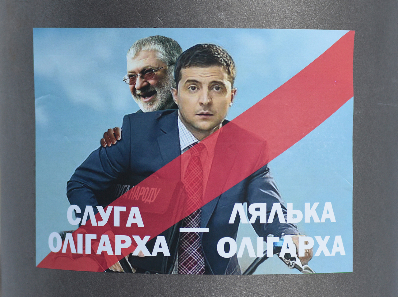 Plakat: Selenski, wie er in seiner TV-Serie den Präsidenten spielt. Hinter seinem Rücken sieht der lachende Oligarch Kolomoiski hervor. Das Bild stammt vom Februar 2019