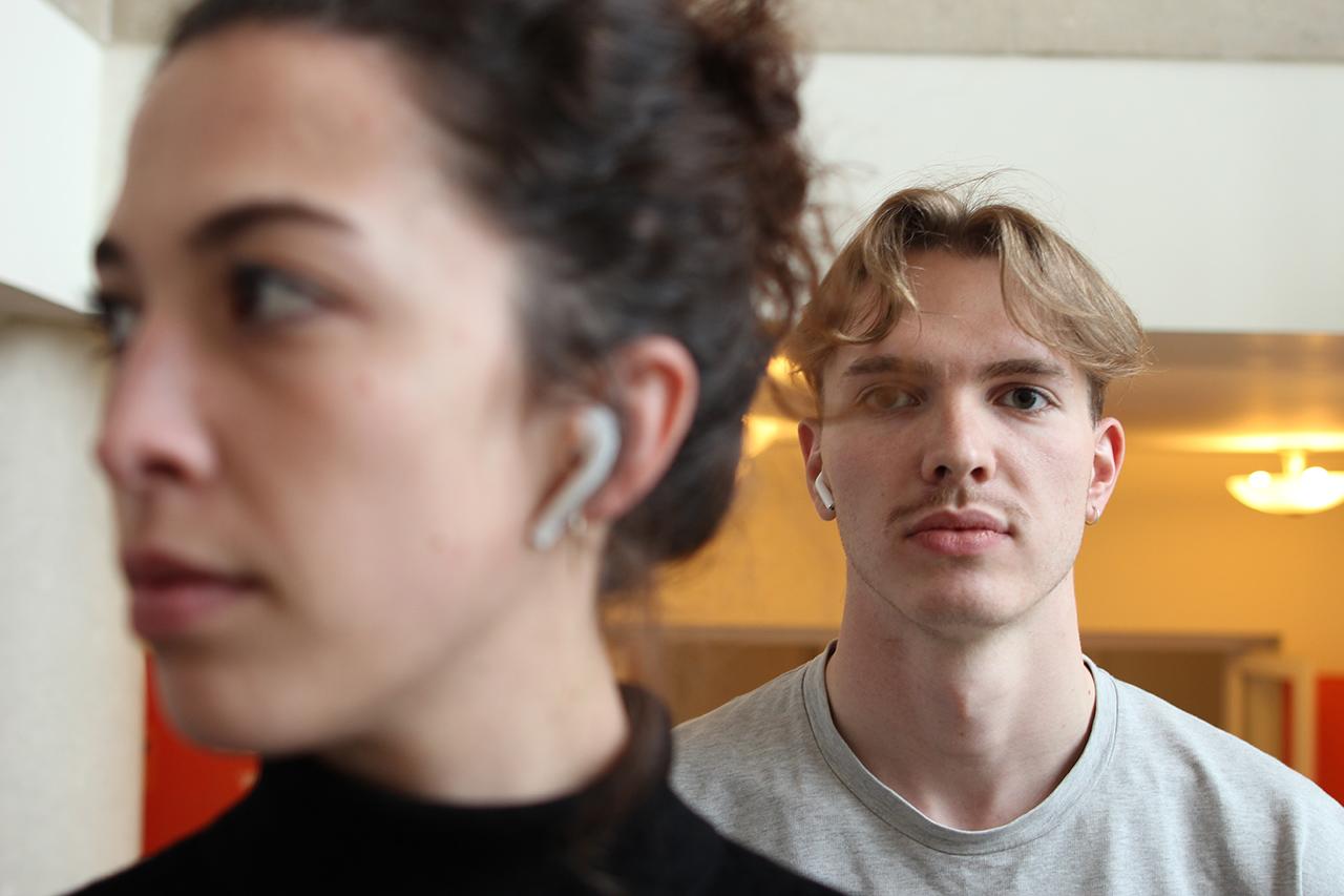 Zwei schöne Menschen mit Bluetooth-Kopfhörern.
