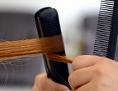 Haare werden mit Glätteisen bearbeitet