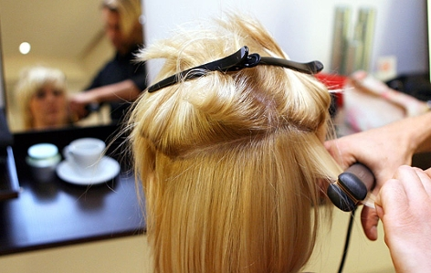 Ein Friseur gestaltet mithilfe eines Glätteisens eine Damenfrisur