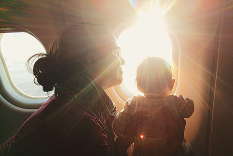 Frau mit Kleinkind schaut aus einem Flugzeugfenster