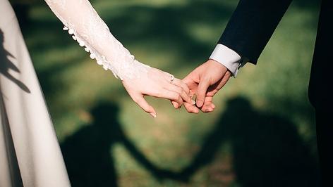Ein Brautpaar reicht einander die Hände