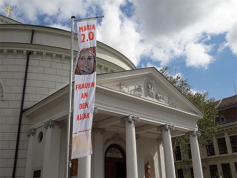 Banner der Aktion Maria 2.0 vor der Pfarre St. Inzersdorf-St. Nikolaus im 23. Bezirk anlässlich des Kirchenstreiks der Frauen am 12. Mai 2019