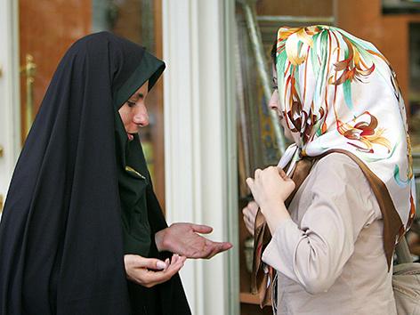 Eine Sittenpolizistin belehrt eine Frau über ihre Kleidung in Teheran, Iran