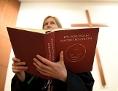 Eine evangelische Pfarrerin mit einem evangelischen Gottesdienstbuch in der Hand