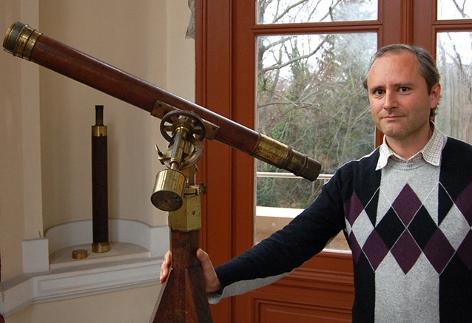 Der Astronom Thomas Posch hält ein älteres Fernrohr an der Universitätssternwarte in Wien