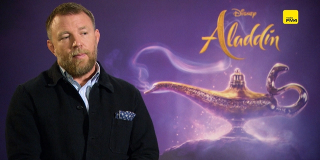Guy Ritchie vor Aladdin-Plakat