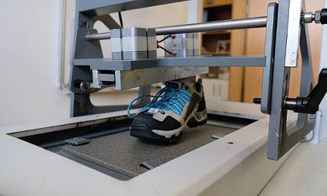 Ein Leichtwanderschuh auf einem Prüfgerät im Labor