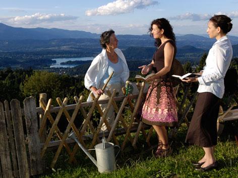 Ein Missionswerbebild der Zeugen Jehovas. Drei Frauen bei einem Gartenzaun mit Wald und Wiesen im Hintegrund