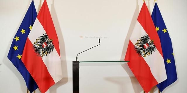 Fahnen und das leere Rednerpult im Bundeskanzleramt vor der Pressekonferenz von Kurz