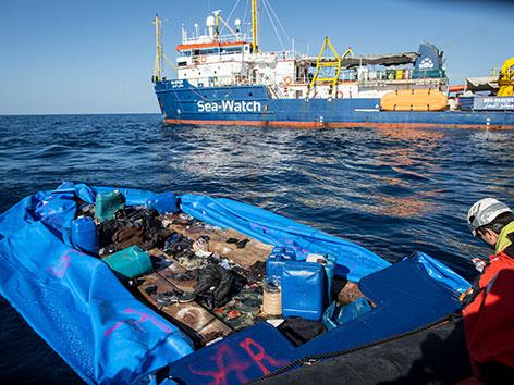 Ein Schiff der Sea Watch neben einem Schlauchboot