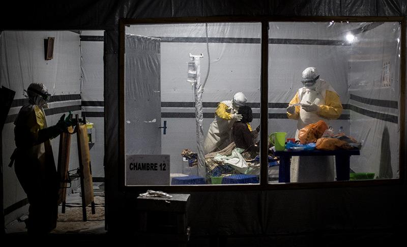 Medizinisches Personal mit Schutzanzügen in einer improvisierten Krankenstation