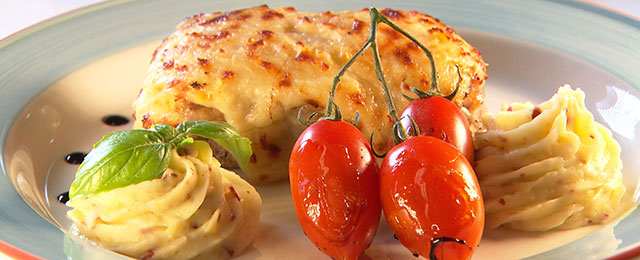 Mit Parmesan überbackenes Kalbssteak auf Teller