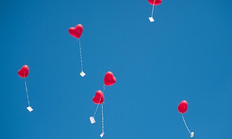 herzförmige Luftballons mit Grußkarten fliegen in den Himmel