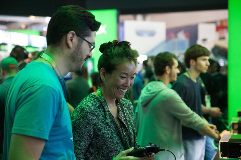 Ein Mann und eine Frau unterhalten sich auf der E3, sie hält ein Gamepad.