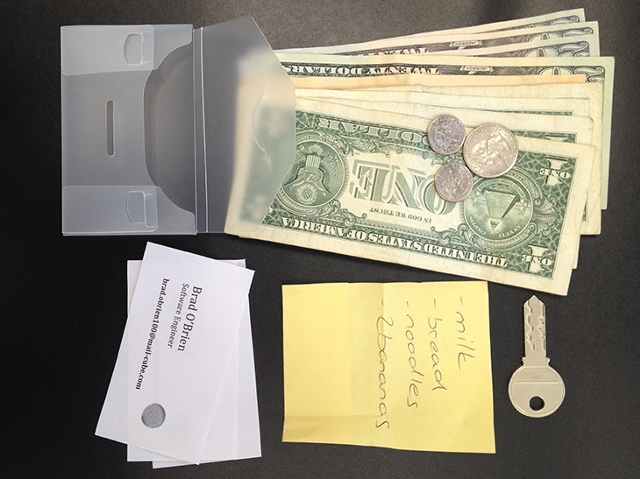 Inhalt einer Brieftasche: Schlüssel, Geld, Visitenkarte und Einkaufszettel