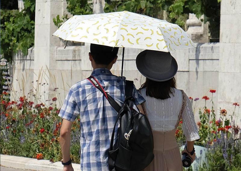 Touristen mit Sonnenschirm vor dem Wiener Stadtpark