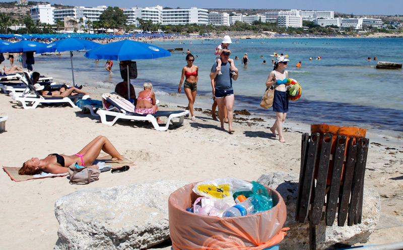 Strand auf Zypern, Mistkübel im Vordergrund und Urlauber