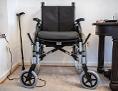 Ein Rollstuhl neben Stock und Tisch mit Medizin