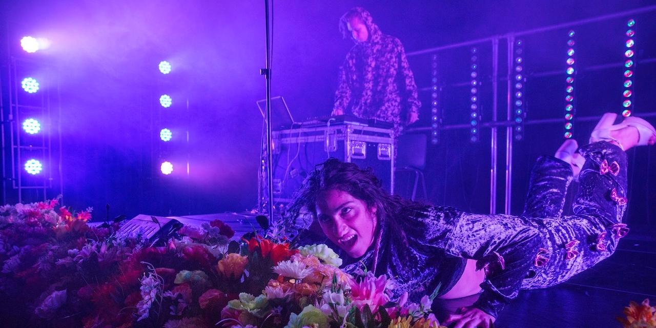 Nas hinter Kunstblumen am Bühnenboden liegend