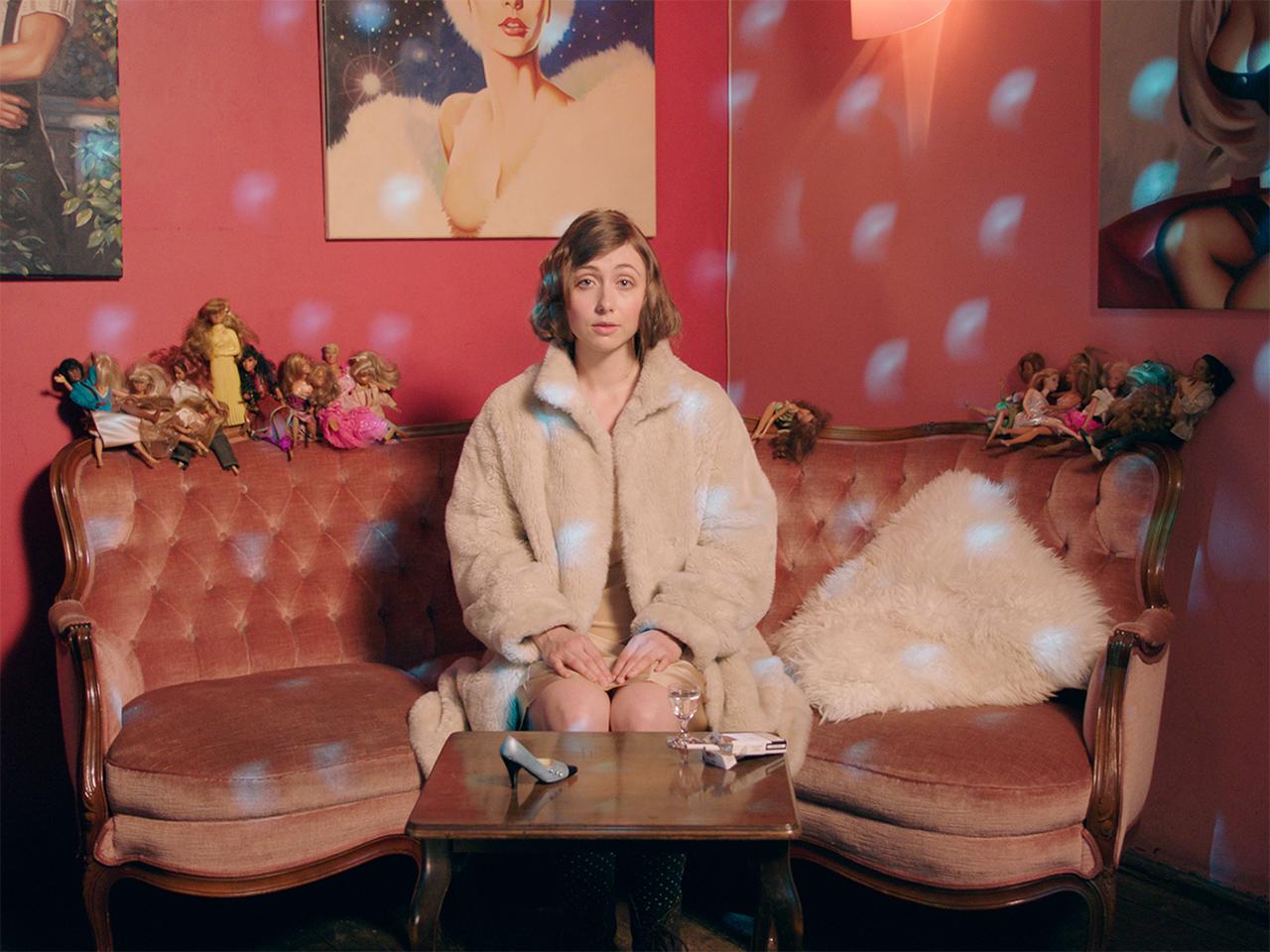 Frau sitzt auf einem Sofa mit vielen Barbies