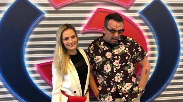 Ö3-Reporterin Tina Ritschl im weißen Blazer und Robert Kratky im Blumenhemd.